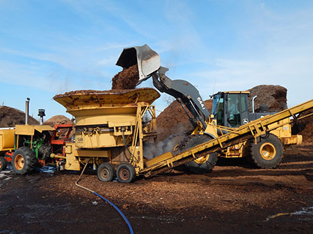 Pay-loader dumping much into grinder