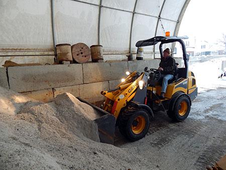 tractor scooping road salt